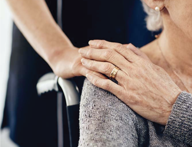 Staff placing their hand on the shoulder of a resident